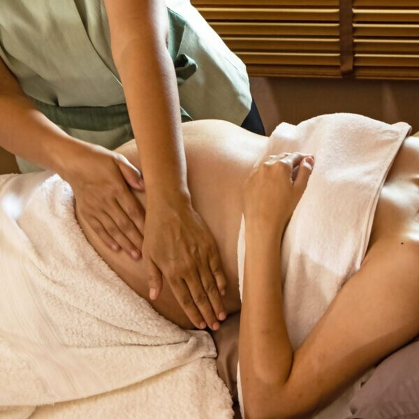 The therapiist massaging pregnant woman,for treat and relax program,at spa therapy