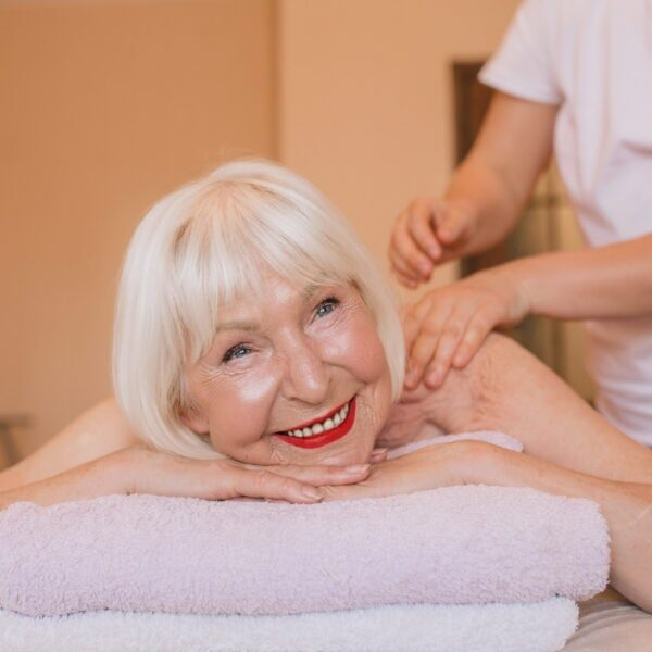 elderly (old) caucasian stylish woman with gray hair laying on a massage. Anti age, healthy lifestyle, massage concept